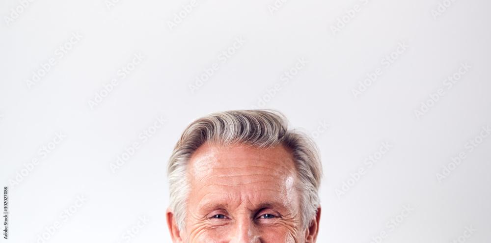 Fototapeta Studio Shot Of Mature Man Against White Background Laughing At Camera Cropped Below Eyes