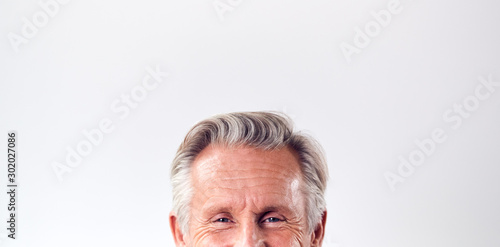 Obraz Studio Shot Of Mature Man Against White Background Laughing At Camera Cropped Below Eyes - fototapety do salonu