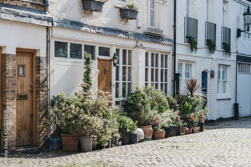 Photo Facade of a typical mews house in London, UK, may plant pots by the entrance