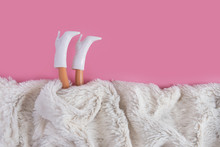 Doll's Legs Sticking Out From Under Synthetic White Fur. Minimalism Concept, 80s Style. Happy Holidays Greeting Card