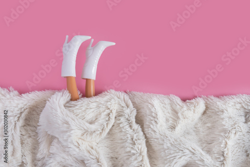 Doll's legs sticking out from under synthetic white fur Wallpaper Mural