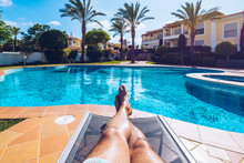 Relaxing At The Swimming Pool. Man Relaxing Next To Swimming Pool. Man Enjoying The Hot Summer At Swimming-pool. Sunbathing By The Swimming Pool, Mans Legs Lying Down On A Sun Lounger Over The Water.