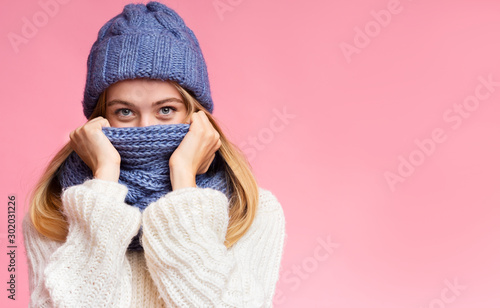 Fotografija Enigmatic winter girl hiding from cold over pink background