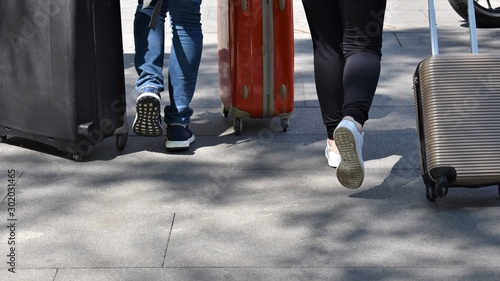 Fotografering  Feet and legs in move of a couple that hurry dragging luggage bags to get to the