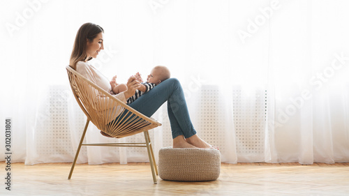 Woman resting in chair with her infant baby on laps Wallpaper Mural