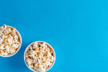 Two White Bowls With Popcron On A Blue Background, Top View, Flat Lay. Free Space For Text. Background With Popcorn.