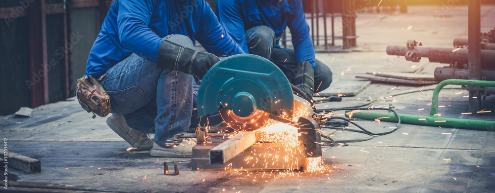 Fototapety, obrazy: Close up view of professional focused two worker man in uniform working on the metal pipe