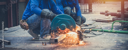 Obraz Close up view of professional focused two worker man in uniform working on the metal pipe - fototapety do salonu