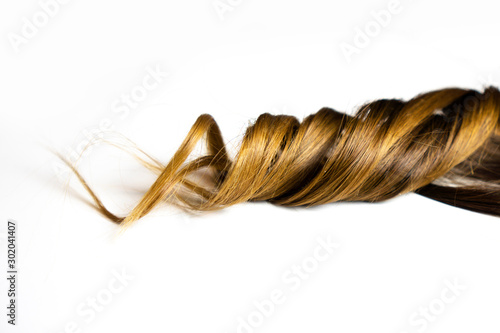 Fotografía  piece of brown curly hair on white isolated background