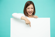 Smiling Happy Asian Woman Standing Behind Big White Poster And Pointing Finger Down To Blank Copy Space Isolated On Light Green Background