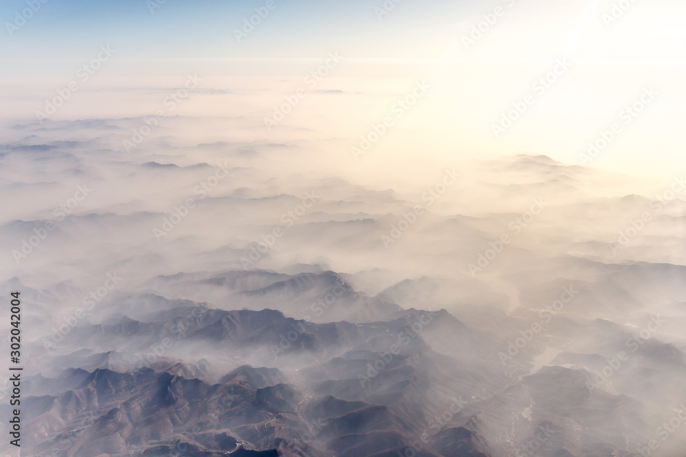 Fototapeta Aerial landscape mountain lost in thick fog in China in the morning sunlight, bird eye view landscape look like a soft water color painting style of chinese