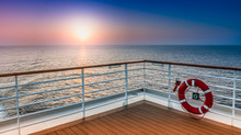 Beautiful Scenic Sunset View From The Deck Of A Cruise Ship With Safety Railing In The Foreground.