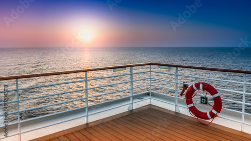 Beautiful scenic sunset view from the deck of a cruise ship with safety railing in the foreground Fototapete