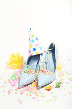 High Heeled Shoes With Confetti, Ribbons And Birthday Cap On White Background. Minimalism Concept