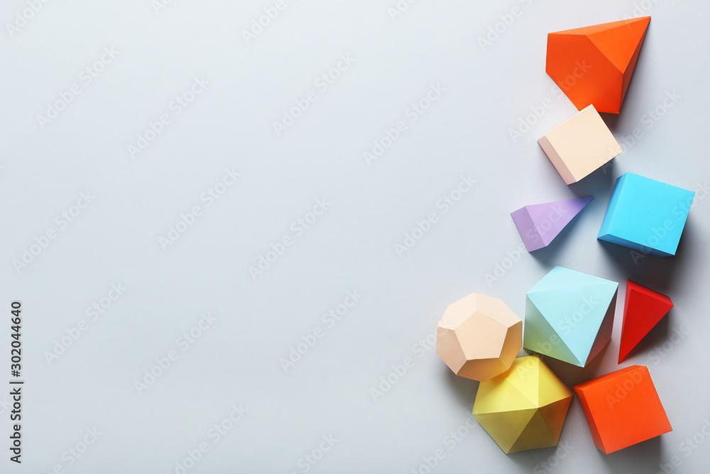 Fototapeta Colorful paper geometric figures on grey background