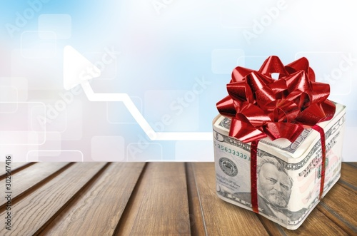 Fotografía  Christmas present with red bow wrapped in dollar banknotes