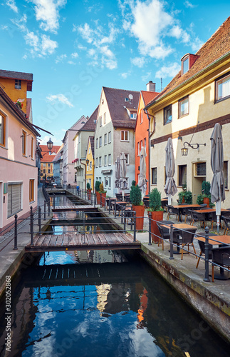 Staande foto Oude gebouw Old street with a water canal and restaurant in Memmingen, Germany.