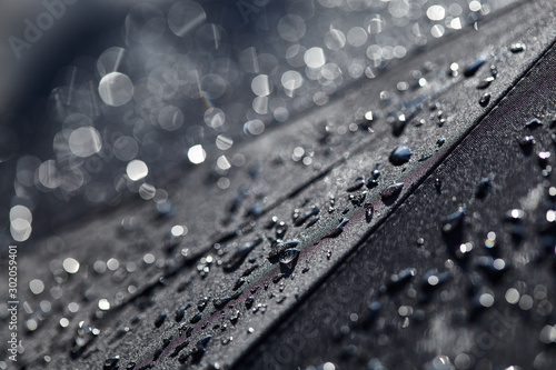 Obraz Abstract black background. Blurred raindrops with bokeh on a black umbrella. Rain Water droplets on black waterproof fabric.Raindrops in the sun. Background with free space. - fototapety do salonu