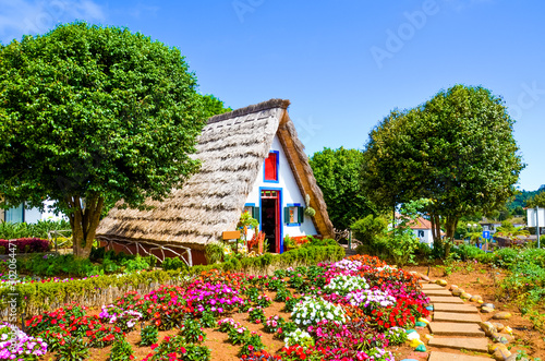 Amazing traditional houses in Santana, Madeira, Portugal. Wooden, triangular houses represent a part of Portuguese heritage. Front garden with beautiful colorful flowers. Tourist landmark