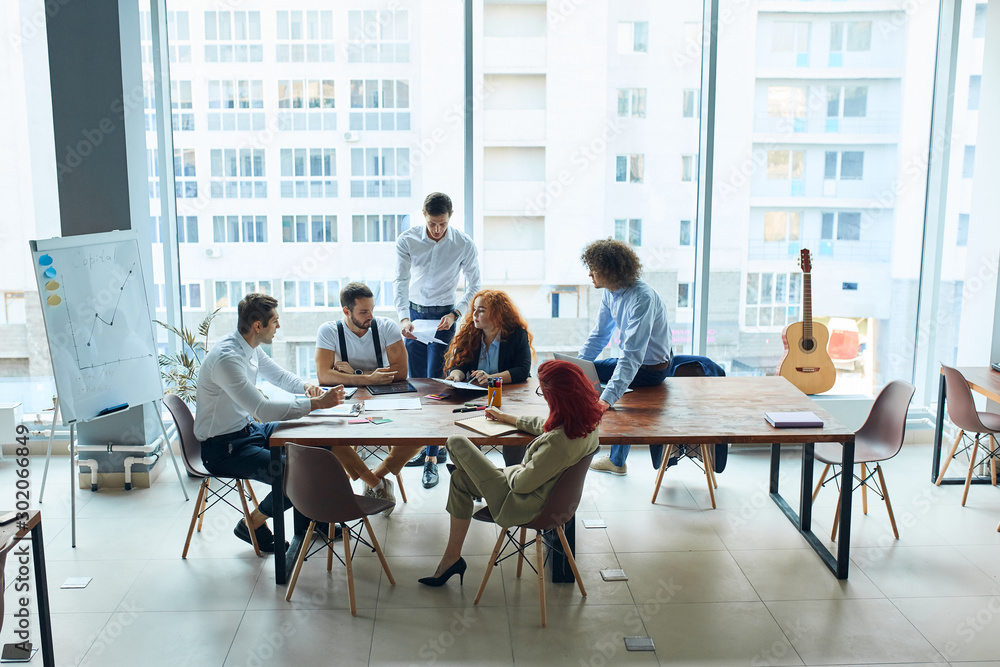 Fototapeta Creative business team of young caucasian peoplecoworking in open space office interior with panoramic window, discuss sitting on table
