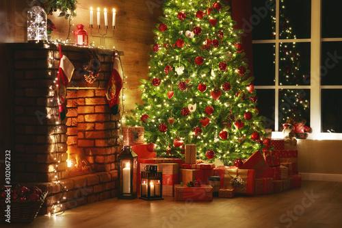 Fototapeta interior christmas. magic glowing tree, fireplace, gifts in  dark  . obraz na płótnie