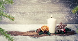 burning candle from advent in front of vintage background and decorative christmas background in snow