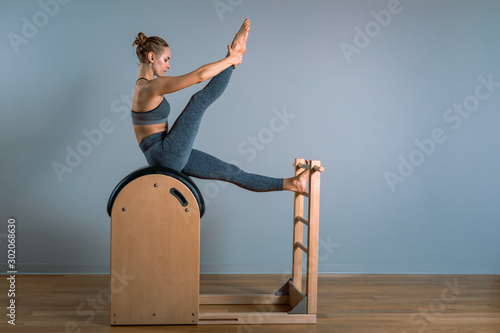 Fototapeta Beautiful positive blond woman is being prepared performing pilates exercise, training on barrel equipment. Fitness concept, special fitness equipment, healthy lifestyle, plastic. Copy space, sport obraz