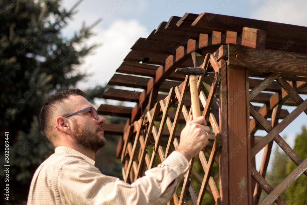 Fototapeta Mężczyzna naprawia ogrodowy mebel. Przybija oderwaną deskę drewnianej pergoli. Odnowa i konserwacja i naprawa drewnianych mebli ogrodowych.
