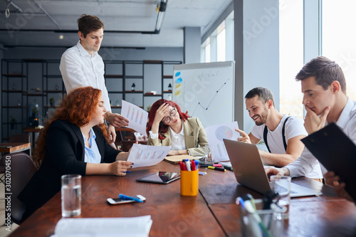 Fototapety, obrazy: Young business people sad with result of their work, disappointed redhaired woman sit in the center of table