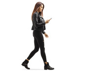 Young Female Walking And Looking At Her Mobile Phone