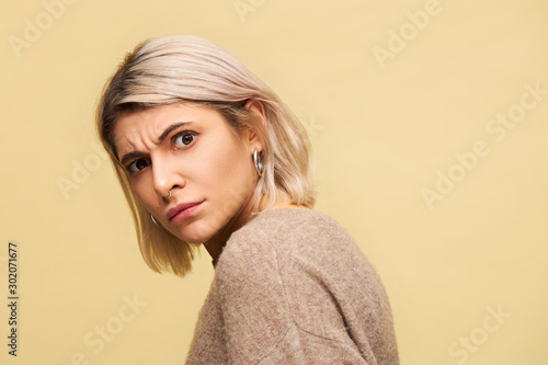 Cuadros en Lienzo Studio shot of blonde young woman turning head to camera frowning not being in m