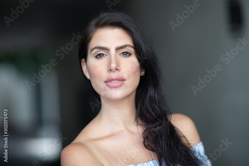 Fotografía  Portrait of beautiful sexy girl with dark hair and bare shoulders looking in the