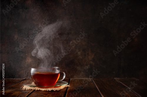 Tuinposter Thee Cup of hot tea with a steam on dark background