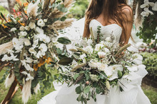 Woman Holding In Hands Big Wedding Bouquet In Boho Style. Dried Flowers, White Roses And Orchids, Bird Feathers In Decor. Floristic Concept.