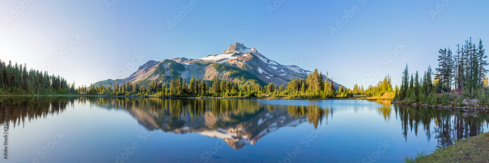 Obraz Volcanic mountain in morning light reflected in calm waters of lake.  fototapeta, plakat