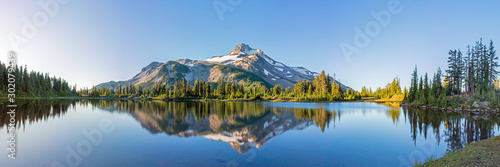 Volcanic mountain in morning light reflected in calm waters of lake.  - 302079439