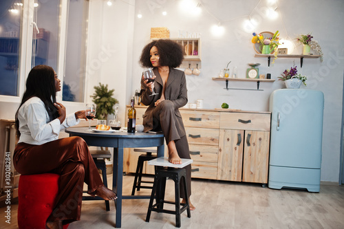 Valokuva  Two african american female friends women spending time at kitchen with wine