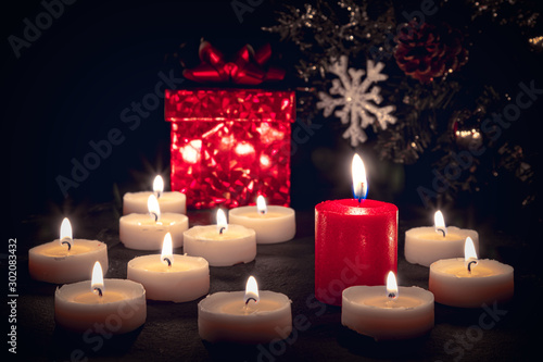 Christmas candles burning at night in front of a red gift box