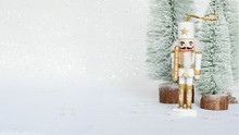 Christmas Nutcracker Toy Soldier Figurine Ornament In White. Decoration For New Year.  Nutcracker On The White Sparkling Background. Advent Concept.