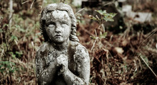 Ancient Statue Of A Praying Angel With Broken Wings As Symbol Of Pain.