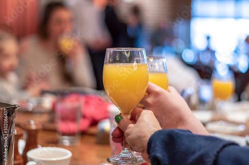 Fototapeta Enjoying mimosas at brunch - two hands clinking glasses