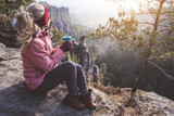 Fototapeta Fototapety na ścianę - Female blond hiker outdoor clothing with coffee cup in hands on limestone rock enjoying sunset back lit view of mountain ridge and forest down the valley. Travel lifestyle adventure concept