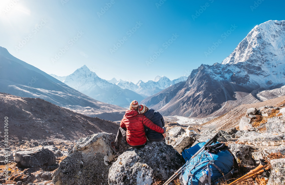 Fototapety, obrazy: Embracing Couple on the Everest Base Camp trekking route near Dughla 4620m. Backpackers left Backpacks and trekking poles and enjoying valley view with Ama Dablam 6812m peak  and Tobuche 6495m