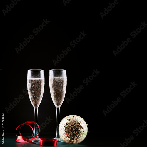 Poster de jardin Alcool Christmas and New Years eve celebration concept: two glasses full of bubbly drink and a bottle of champagne on a table with Christmas decorations.