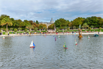 Fototapeta na wymiar Multi-colored boats float in a pool around a fountain in Luxembourg Park. August 5, 2019. Paris. France.
