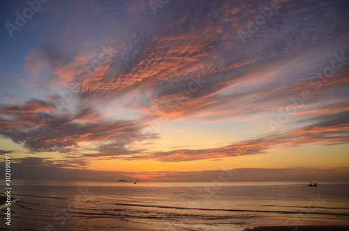 A vibrant orange coloured altocumulus cloud coastal sunrise seascape in a blue sky Wallpaper Mural