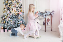 Two Cute Adorable Little Siblings Brother And Sister Having Fun Playing With Retro Wooden Wheel Horse Toy Near Christmas Tree In Cozy Living Room. Portrait Of Funny Pair Smiling Adorable Blond Kids