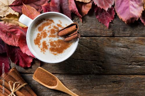 Fototapeta  Top view white cup of salep milky hot drink of Turkey with cinnamon sticks, powd