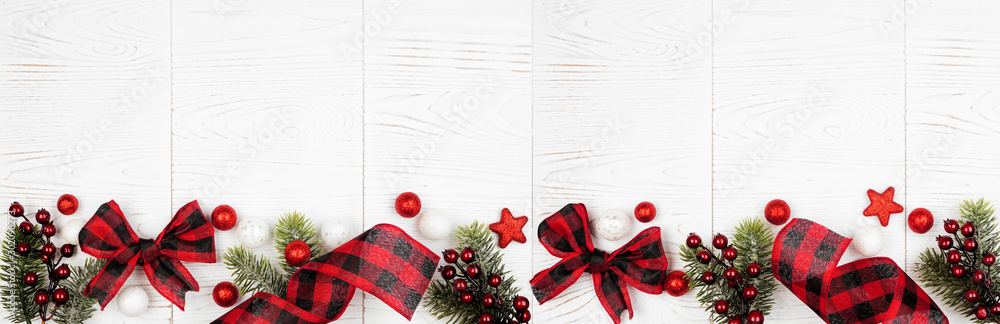 Fototapety, obrazy: Christmas border banner of ornaments, branches and red and black checked buffalo plaid ribbon. Top view on a white wood background.