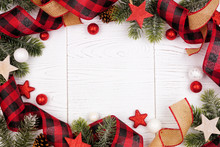 Christmas Frame Of Ornaments, Branches, Burlap And Red And Black Buffalo Plaid Ribbon. Overhead View On A White Wood Background.